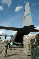 Pallet of humanitarian aid being loaded onto a military cargo plane.