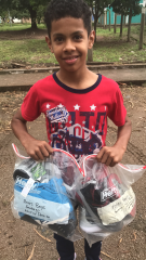 Honduran boy with two bags of clothes and shoes.